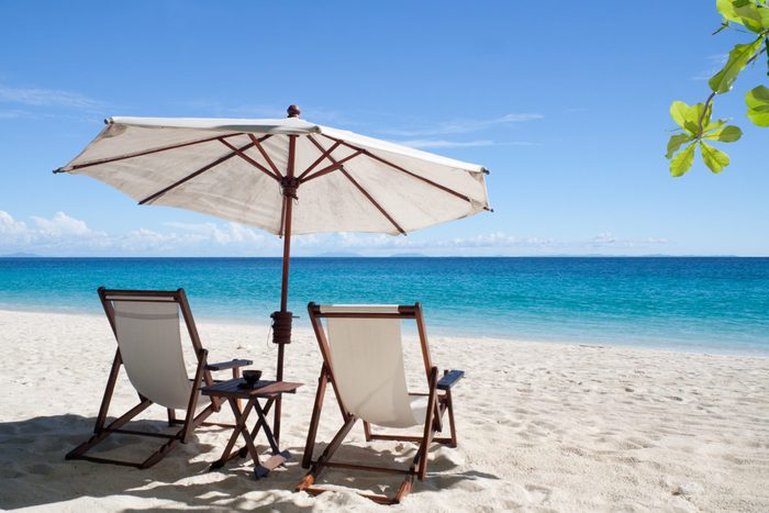 Deckchairs and parasol on the white sand beach facing the lagoon