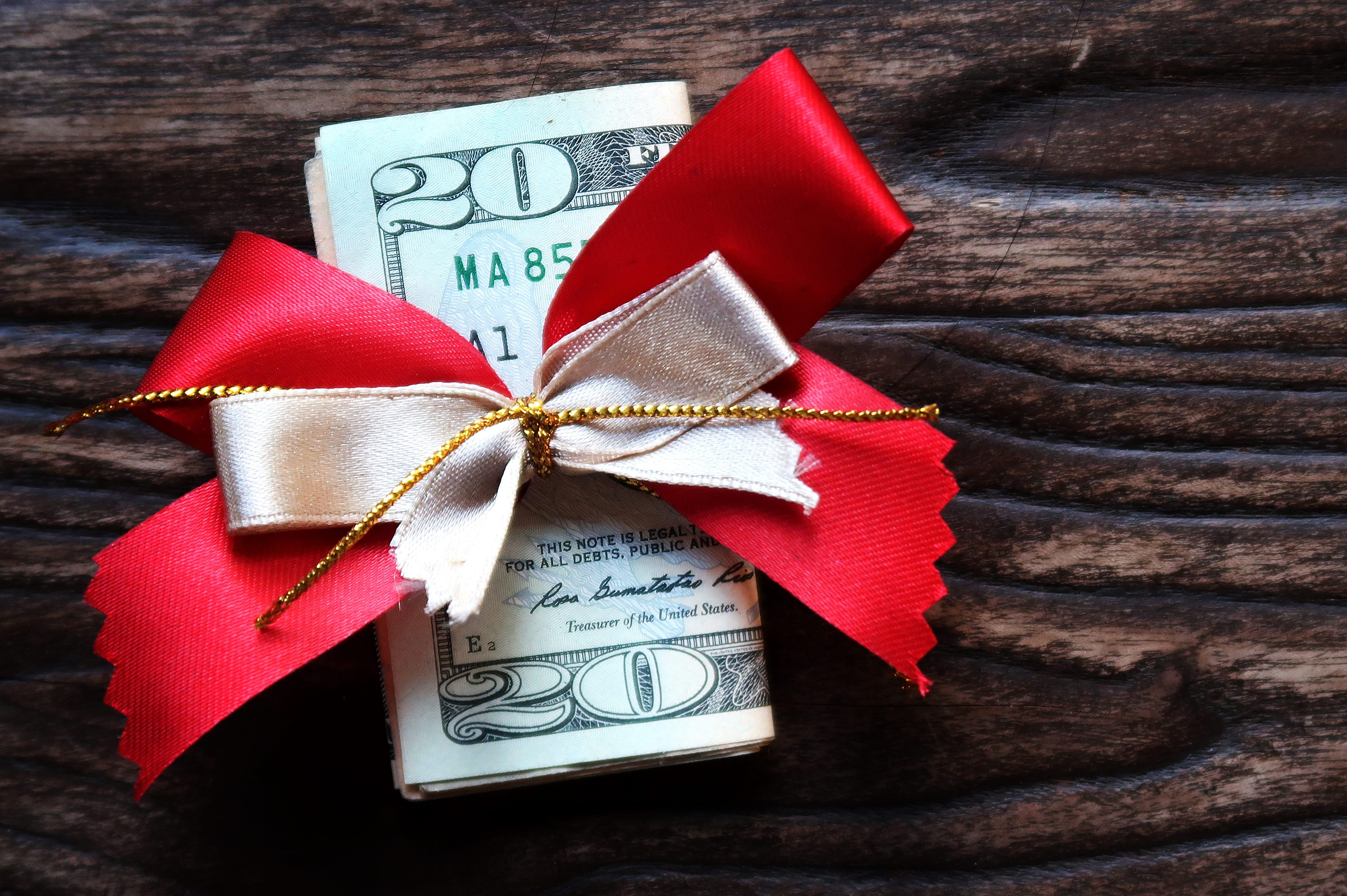 Money gift - A dollar banknote with beautiful red gold ribbon- on grunge old wood background