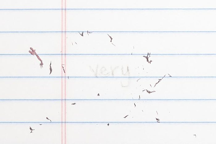 """erased text """"very"""" with eraser shavings on loose leaf paper"""