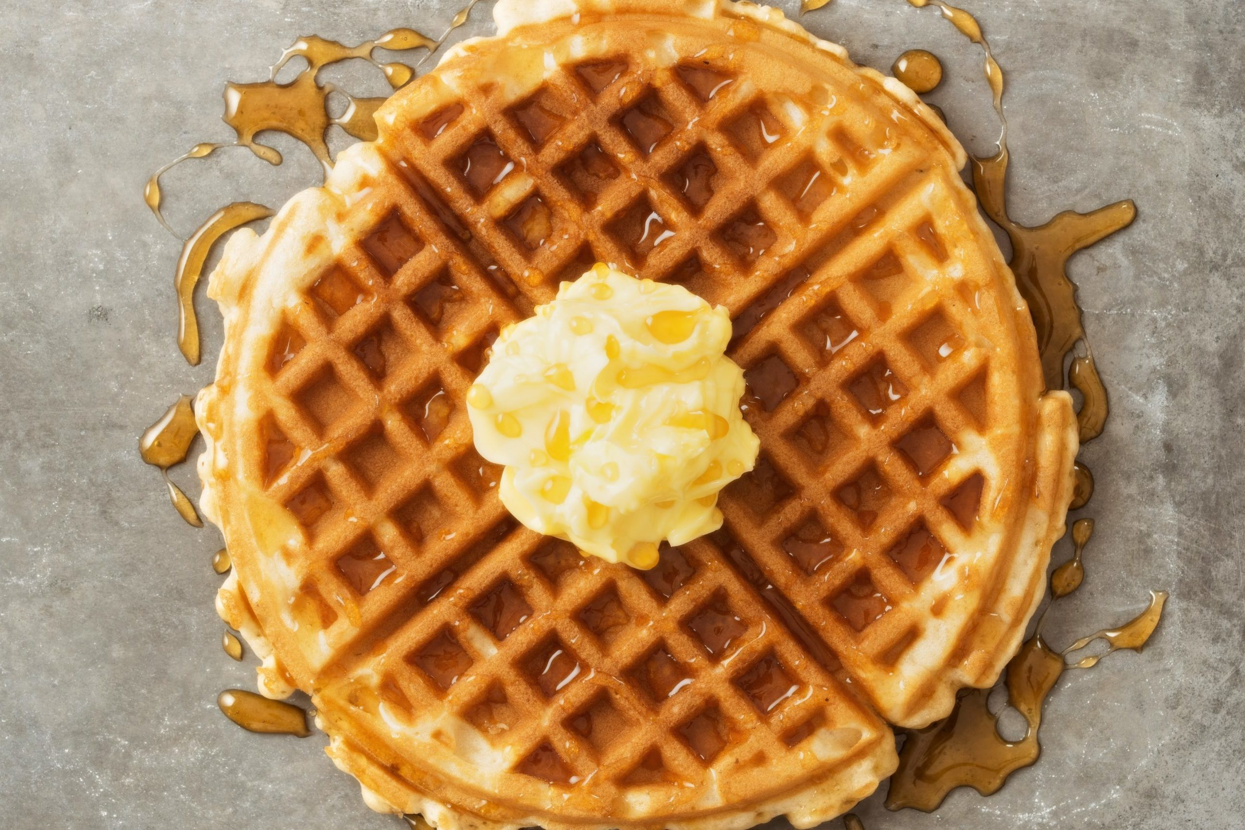 close up of rustic traditional waffle with butter and maple syrup