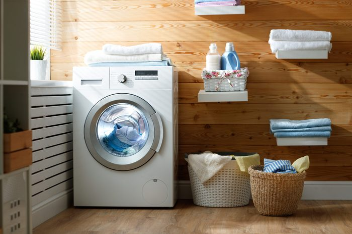 Interior of a real laundry room with a washing machine at the window at home