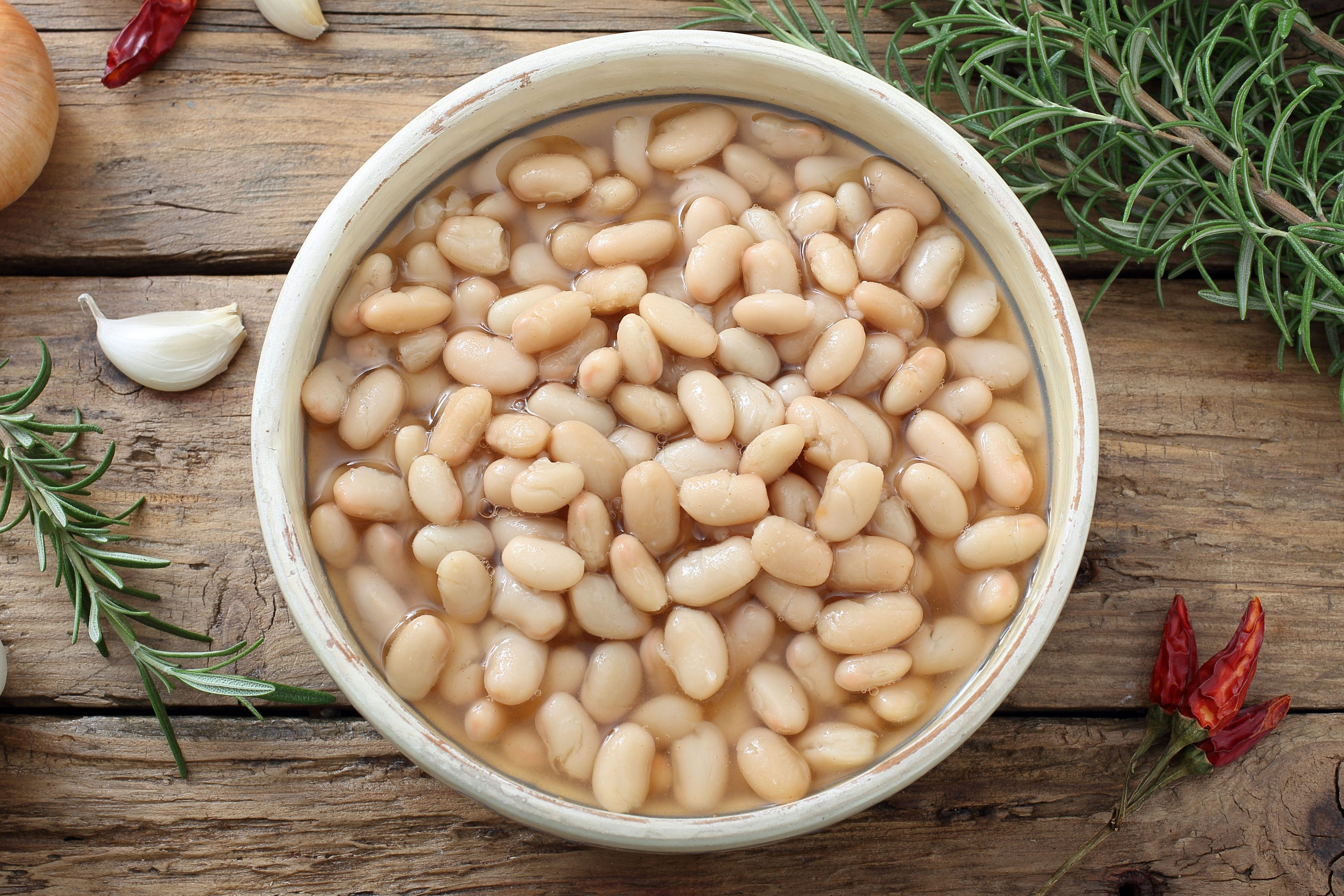 boiled white beans in ceramic bowl on a rustic chicken table background