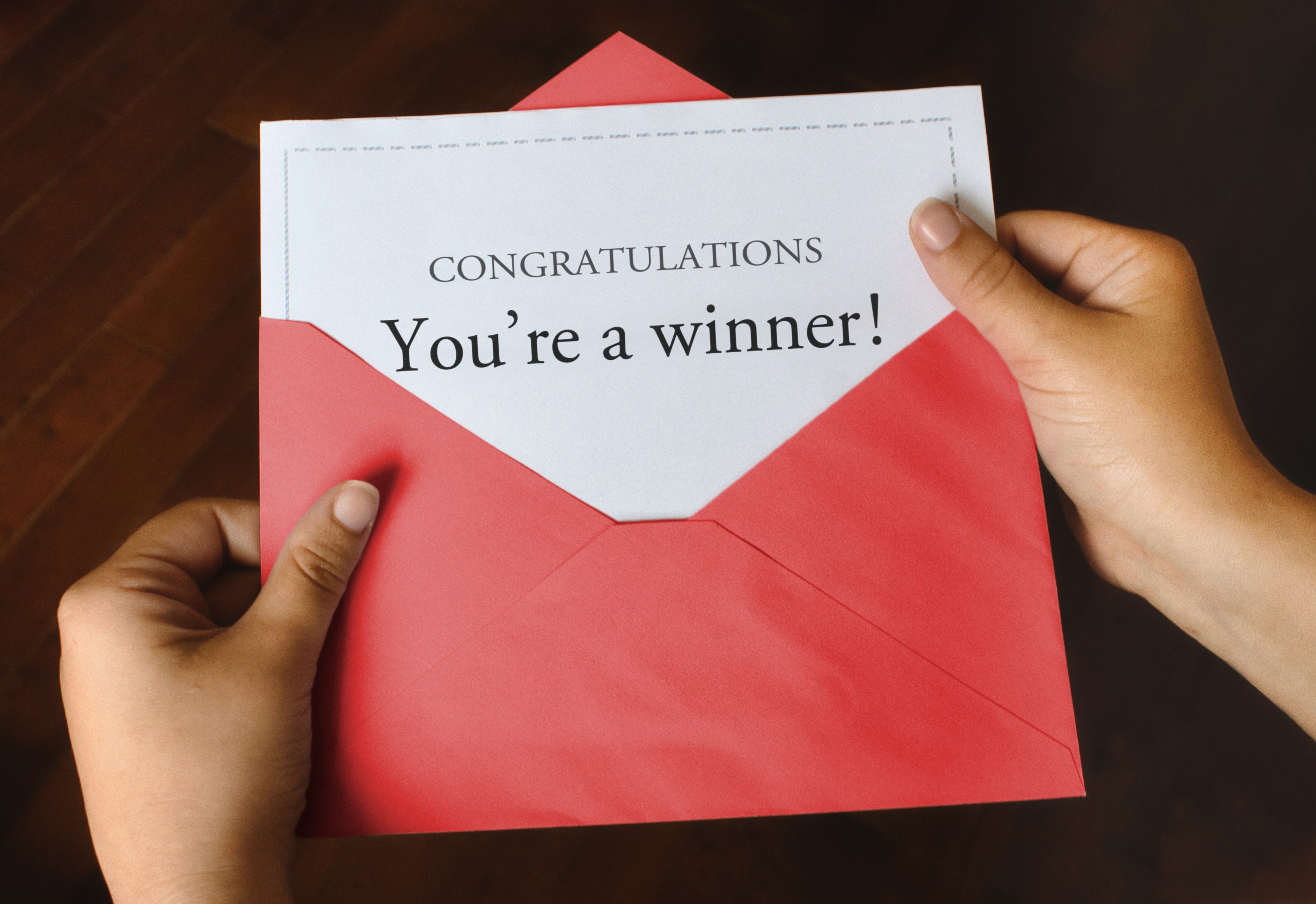 An open red envelope with a letter that says Congratulations You're a winner! with female hands holding it up