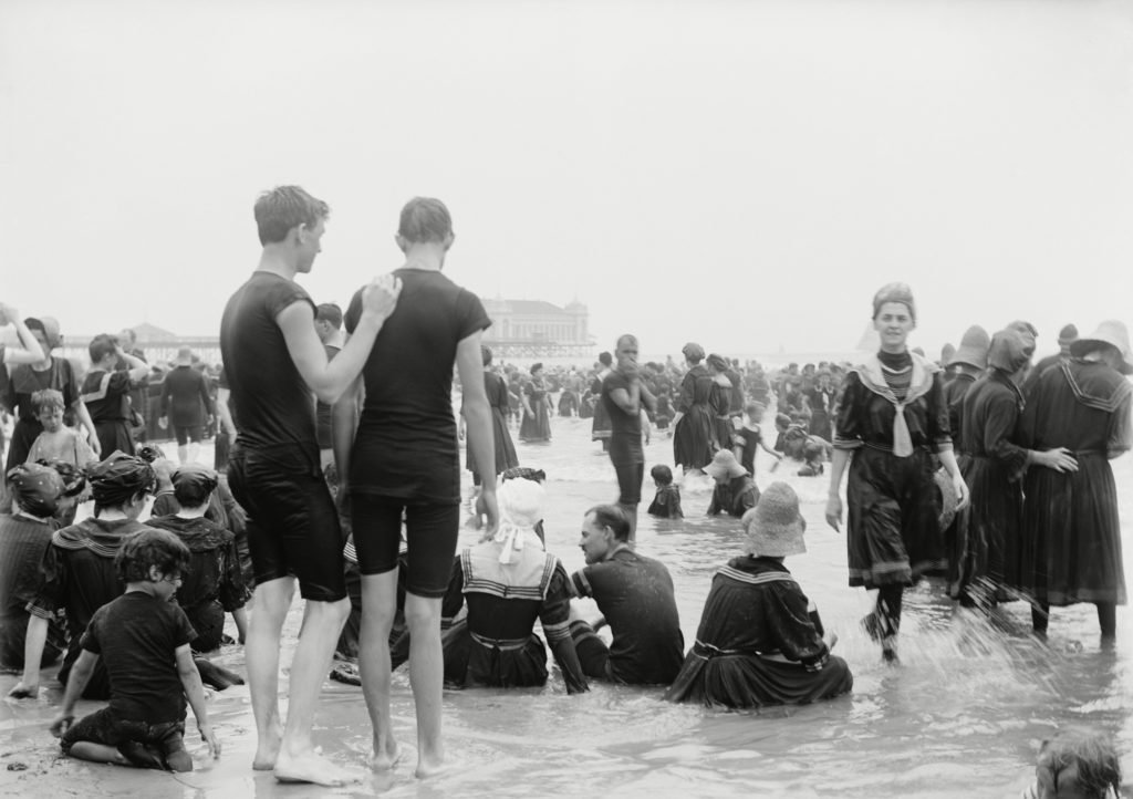 Men, women, and children enjoying the surf at Atlantic City, New Jersey, c. 1890-1900. Most women wear a middy style swimming dress with fill long sleeves and stockings. The men wear short sleeves t-shirts with long shorts