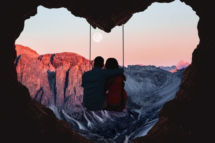 A couple sitting on a swing in front of a heart cave at sunset