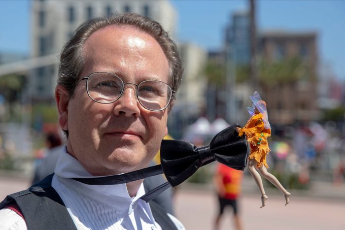 a man dressed up for comic-con with a fairy pulling on his bowtie