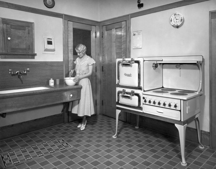 Beaver Dam, Wisconsin: c. 1928. A woman cooking in her kitchen, which is equipped with a Monarch electric stove.