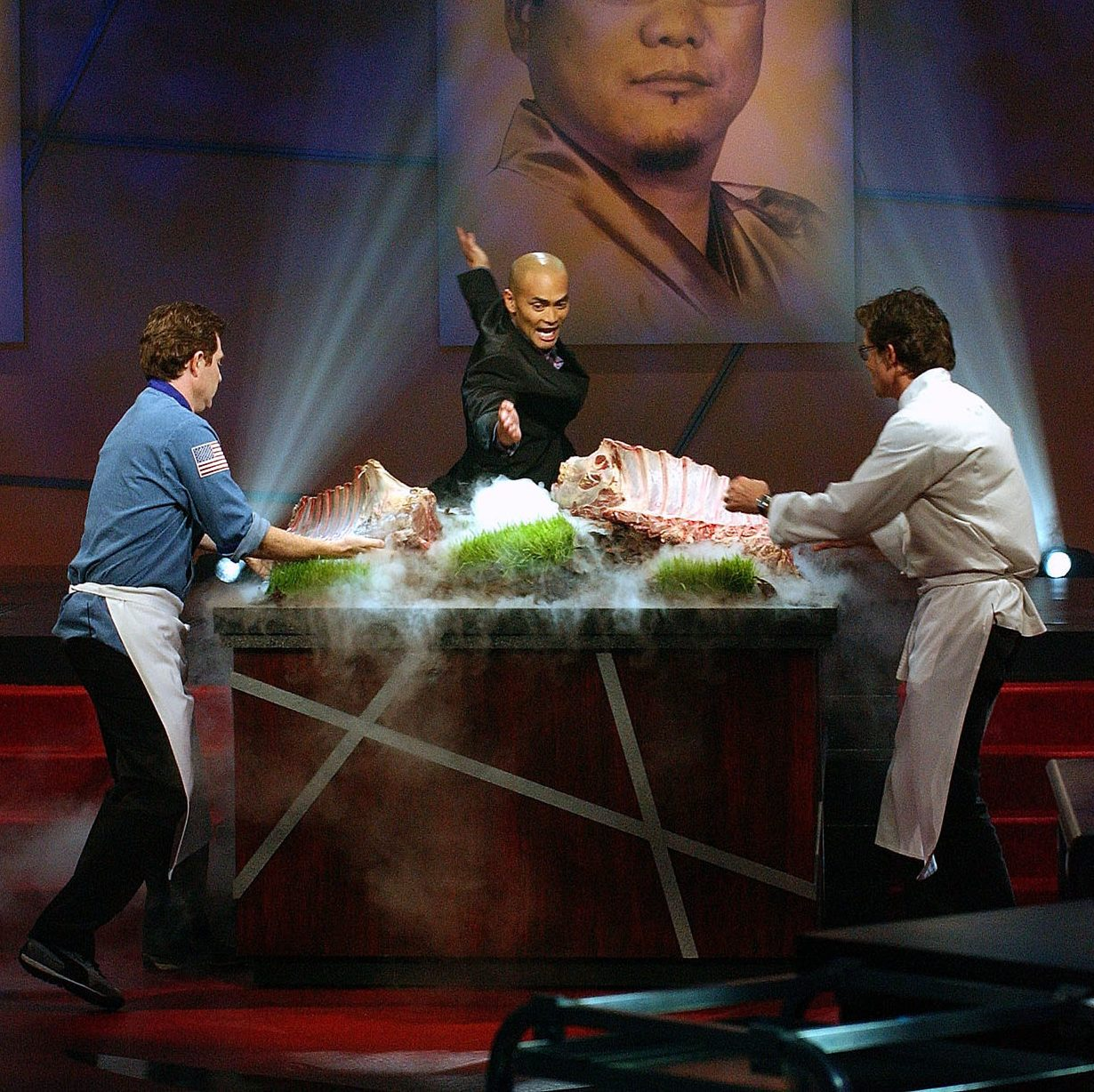 """Mandatory Credit: Photo by Jim Cooper/AP/Shutterstock (6405851b) Iron Chef Bobby Flay, left, of Mesa Grill in New York, and challenger Rick Bayless, right, of Frontera Grill in Chicago face off during a taping of the """"Iron Chef America"""" in New York, . Man in center is unidentified Q&A BOBBY FLAY, NEW YORK, USA"""