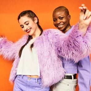 Two young women in purple clothes dancing in front of an orange wall