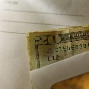close up shot of envelope cash money tip mailman