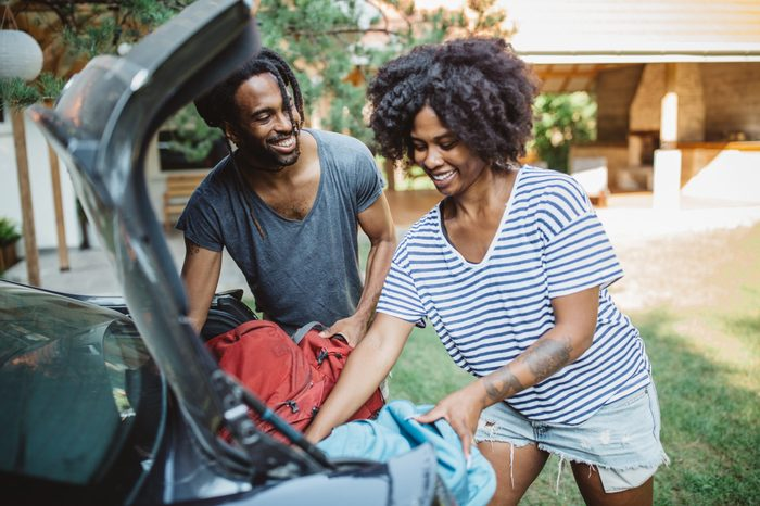 Young African-American couple loading/unloading a car. Putting backpacks in open trunk.