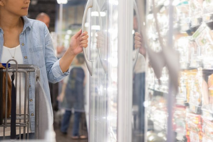 Woman opens door in refrigerated section in store