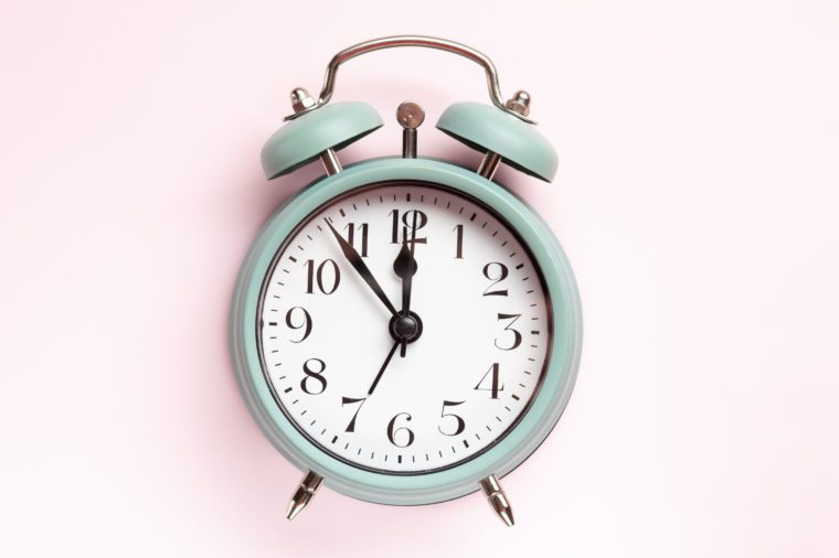 Retro style alarm clock over the pastel pink background