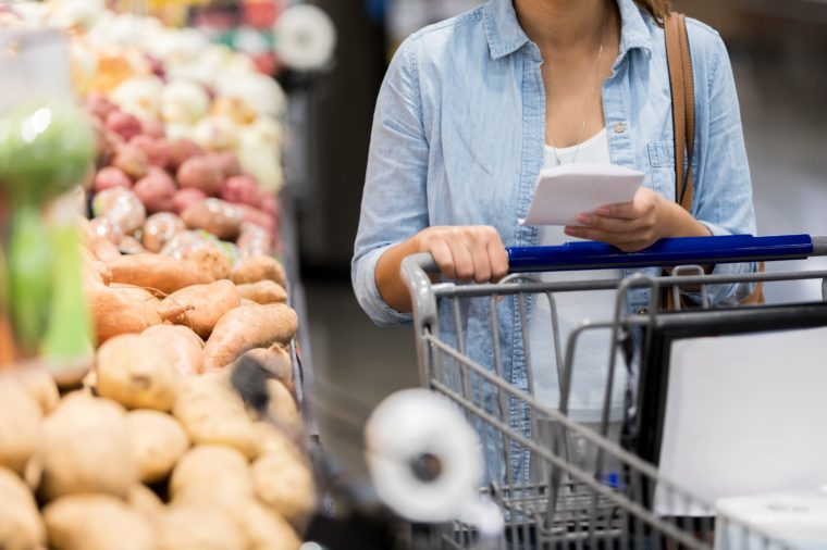 An unrecognizable woman pushes her cart past the potatoes in the grocery store.