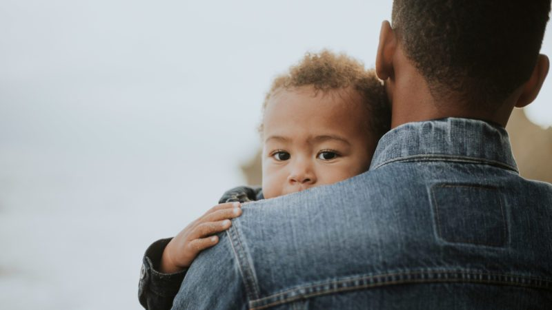 young boy in his dad's arms outdoors. black history month.