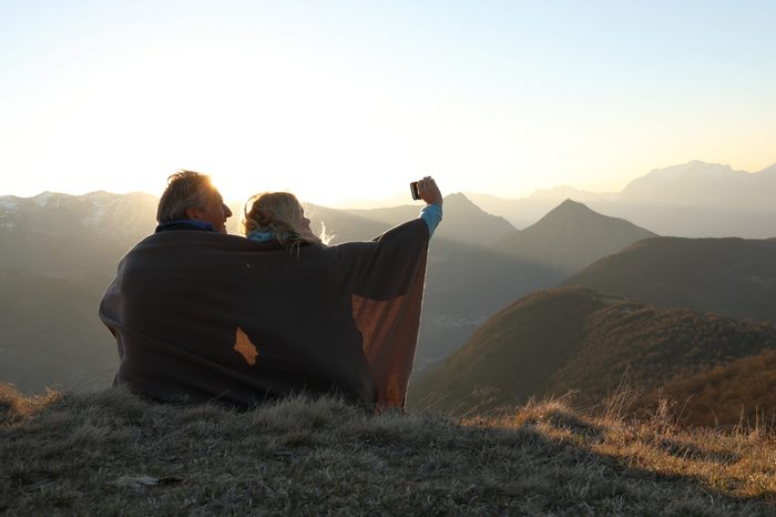 Couple wrapped in blanket take photo