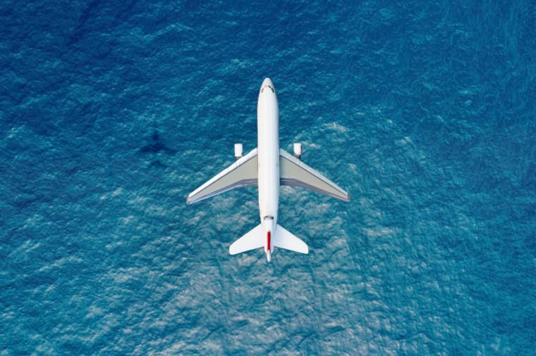 aerial view of airplane flying over water