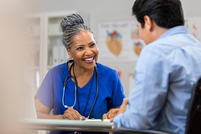 a friendly african american nurse with hair in braids sits with a patient. she smiles and laughs.