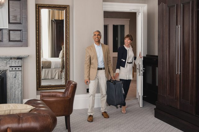 man and woman walk into their hotel room suite and are pleased with what they see
