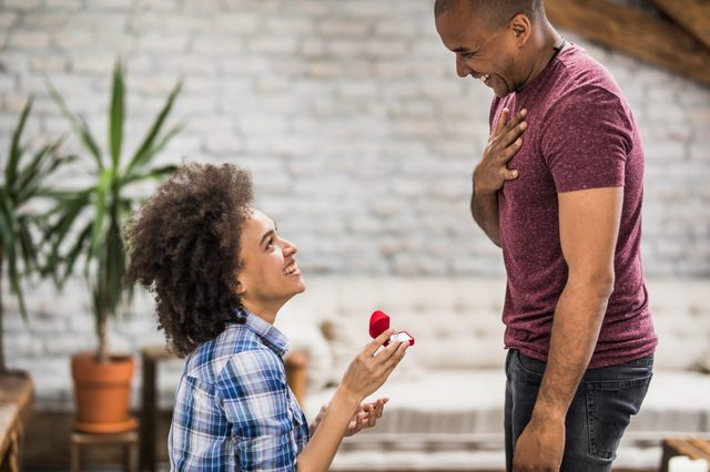 Happy black woman proposing to her boyfriend in the living room.