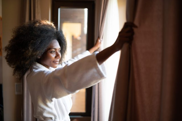woman pulling open the curtains in a hotel room