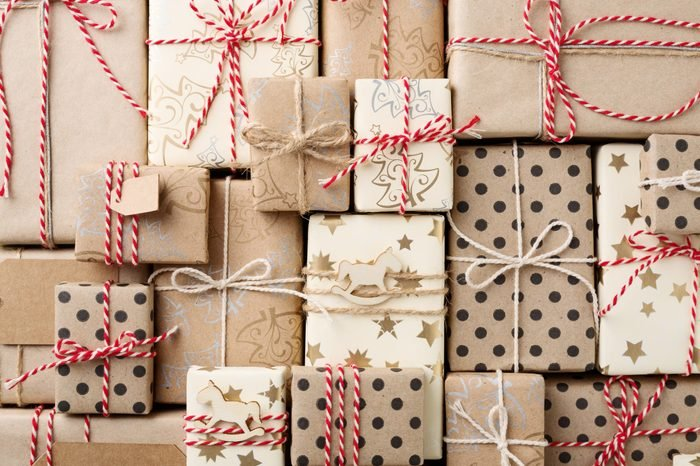 Christmas background with many decorative homemade gift boxes wrapped in brown kraft paper and red white twine. Flat lay.