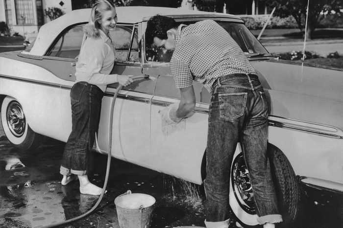 A young man and woman, wearing rolled up jeans, smile while washing the car in a driveway in the 1950's