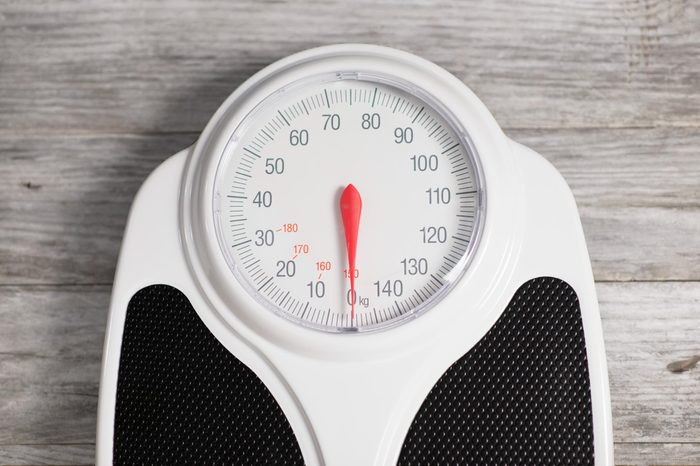 overhead view of a bathroom scale dial on wood background