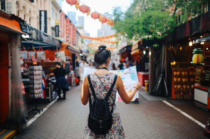 young solo traveler. woman looking at a map while walking through the market.