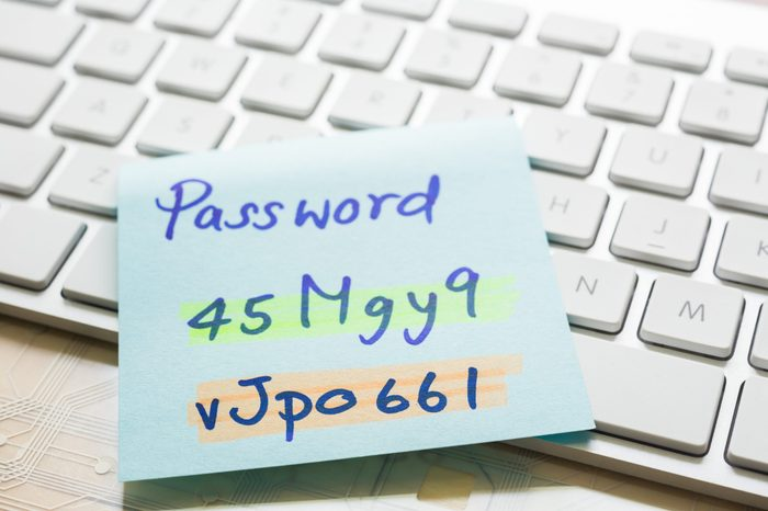 """Handwriting passwords with """"nhighlight colors written on blue paper note on top of modern white keyboard with wooden office table on background. Login access, data privacy and cyber security concepts."""