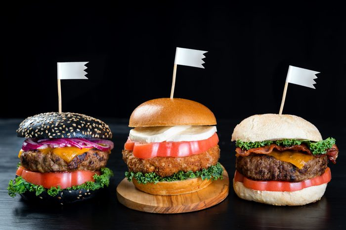 three very different burgers each with a flag on a toothpick sticking out the top of them