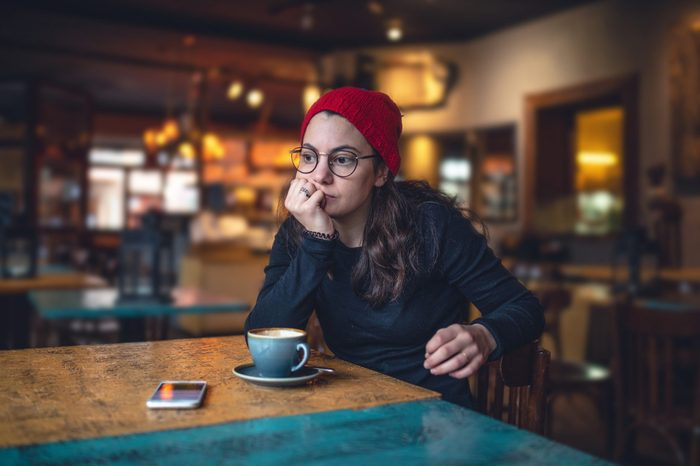 lonely girl in a coffee shop looking worried