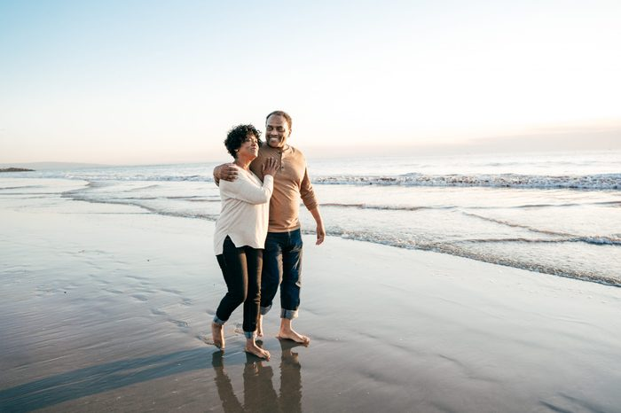 Senior men walking with senior woman on the beach happy loving couple