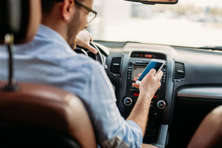 man looking at his phone while texting and driving