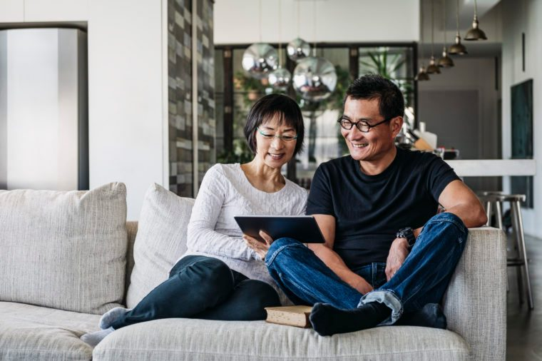 Senior woman and mature man using digital tablet at home in living room, talking online, facetime, social media