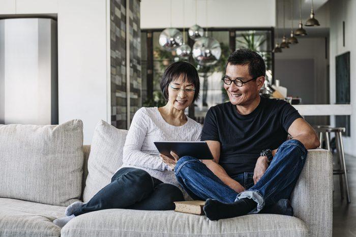 Senior woman and mature man using digital tablet at home in living room, talking online, facetime, social media