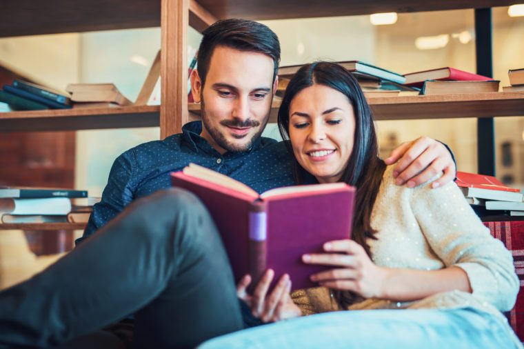 Young couple reading a book in library, surrounded with books on the wooden shelves. Education, dating, university, relationships, lifestyle concept