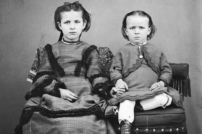 Portrait of two unidentified children holding hands while posed on homemade fancy chairs, Wisconsin, 1869. The girl is dressed in a hand-me-down dress cut from a heavy wool woman's dress while the boy on the right wears an old-fashioned infant's dress which has become too small for him