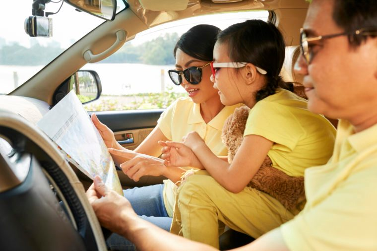 Mature Vietnamese man with his wife and daughter sitting in car and searching destination point on a map