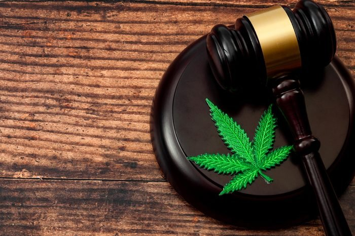 gavel and cannabis leaf patch on wood background