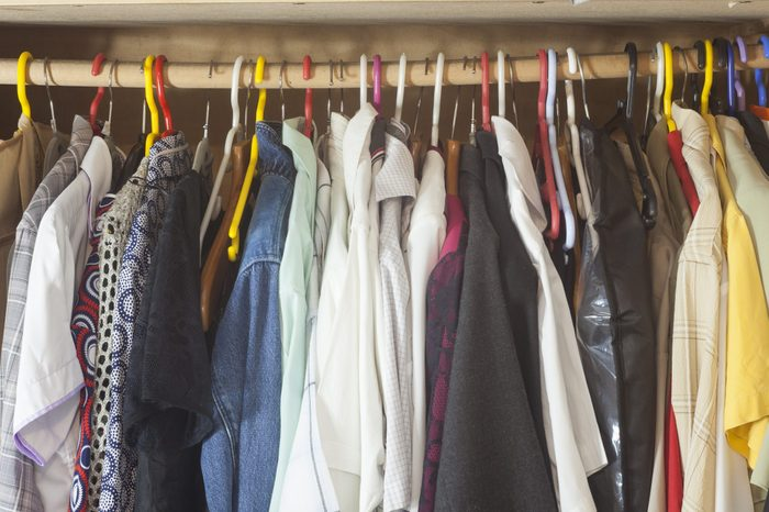 many clothes in closet.