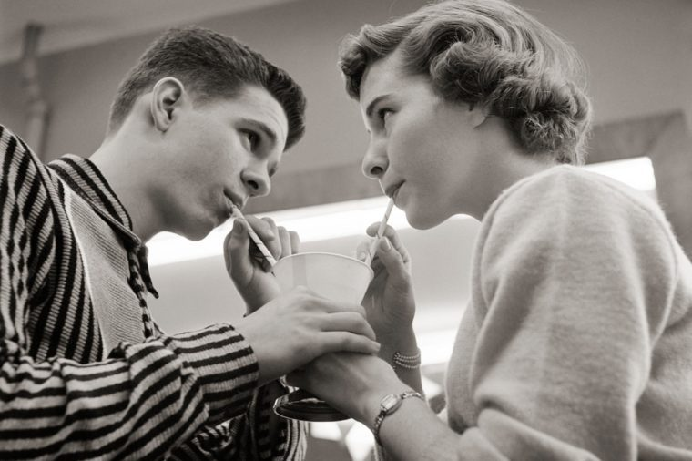 1950s TEENAGE COUPLE SHARING ICE CREAM SODA AT LUNCH COUNTER TWO STRAWS ONE DRINK