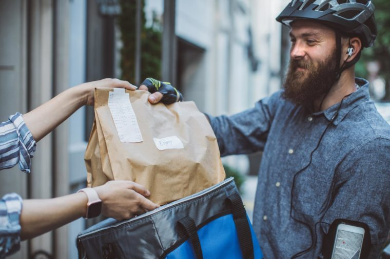man with a bicycle helmet delivering food take out order to a woman