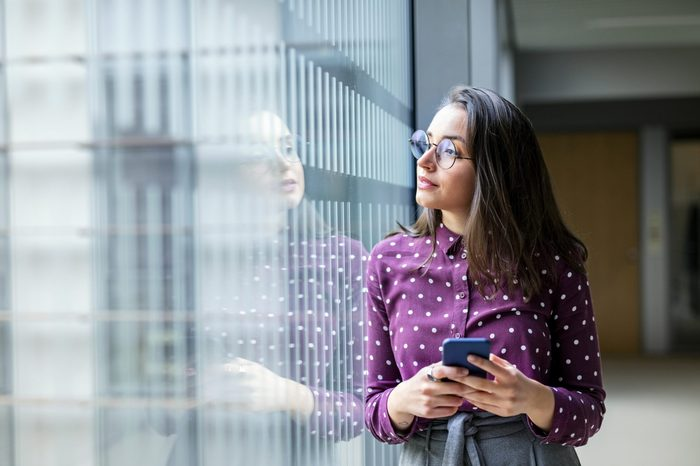 Shot of a young female business professional with a cell phone standing by a glass wall in office and looking away