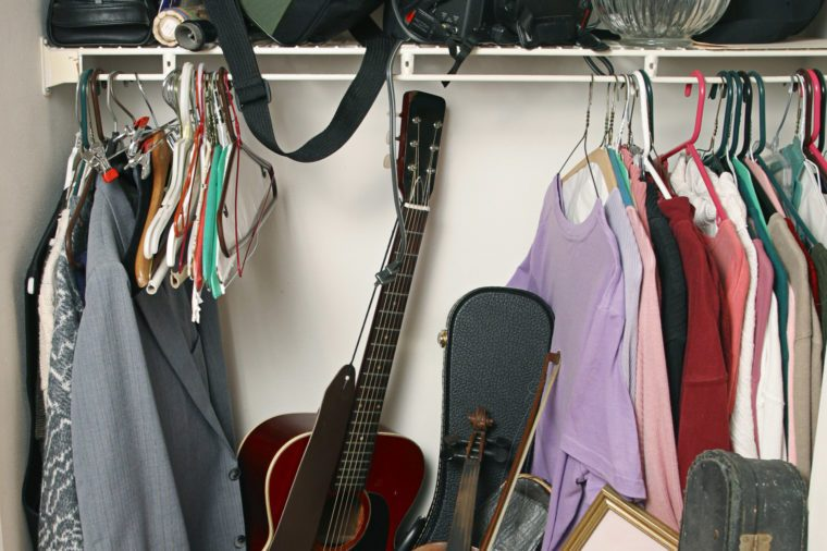 closet with clothes, bags, instruments