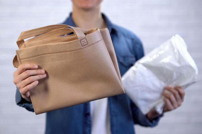 person holding resuable bag in one hand, plastic in another