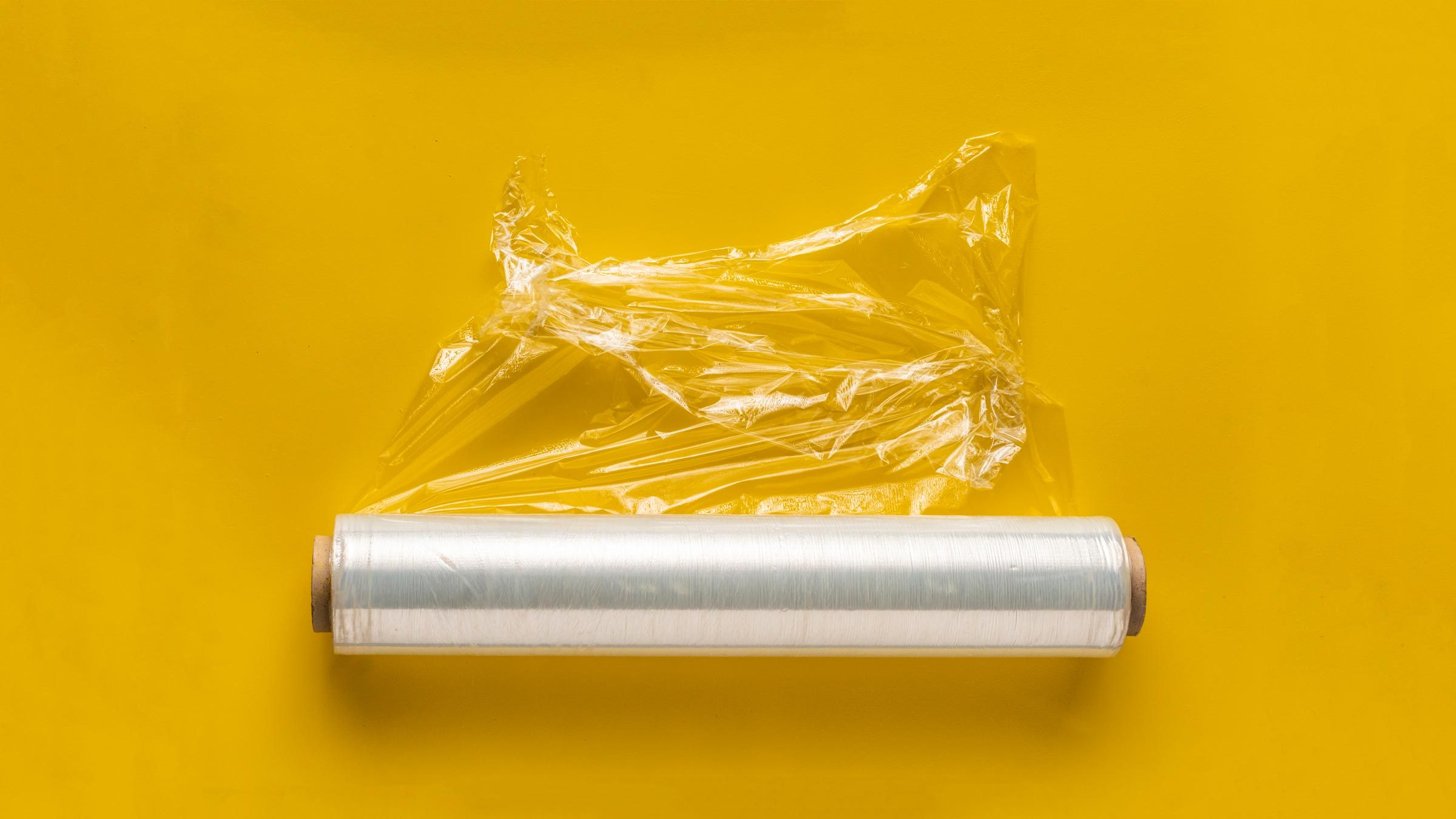 roll of plastic wrap on yellow background