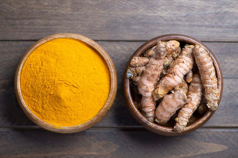 View from above bowl with turmeric powder next to another bowl with turmeric root on brown wooden table.