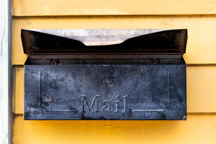 Old retro vintage door mail box, mailbox attached to house home wall exterior painted in yellow color