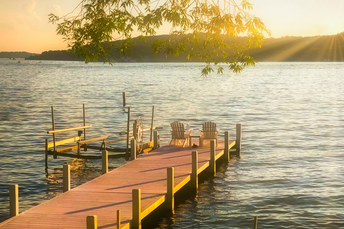 A picturesque Lake Geneva Pier with 2 Chairs at Sunset. Lake Geneva, Walworth County, Wisconsin, USA